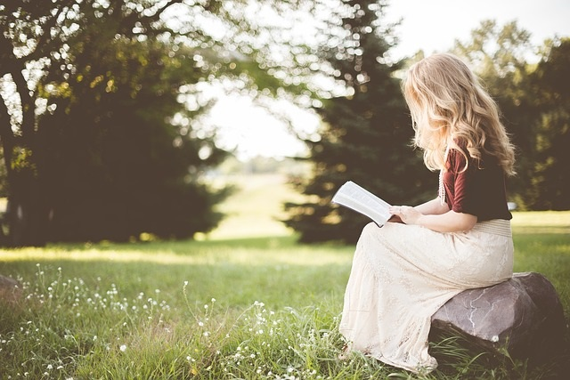 Woman sitting on a rock reading her Bible for Quiet Time.
