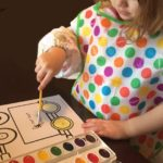 Little girl watercoloring an ABCJesusLovesMe worksheet.