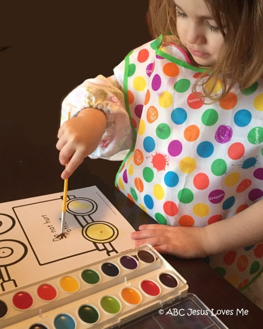 Little girl painting with watercolors the ABCJesusLovesMe worksheet.