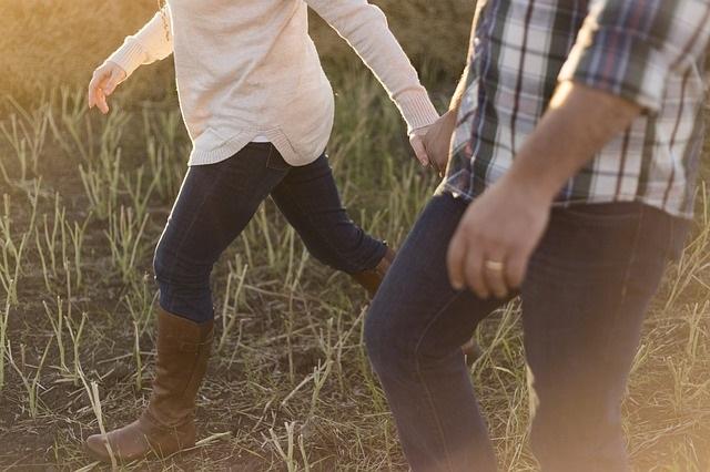 Couple walking in field.