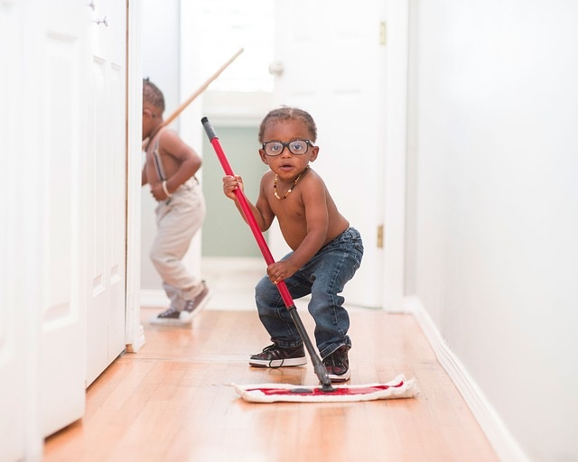 A little boy mopping the floor.