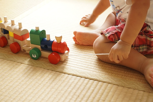Toddler playing with trains.