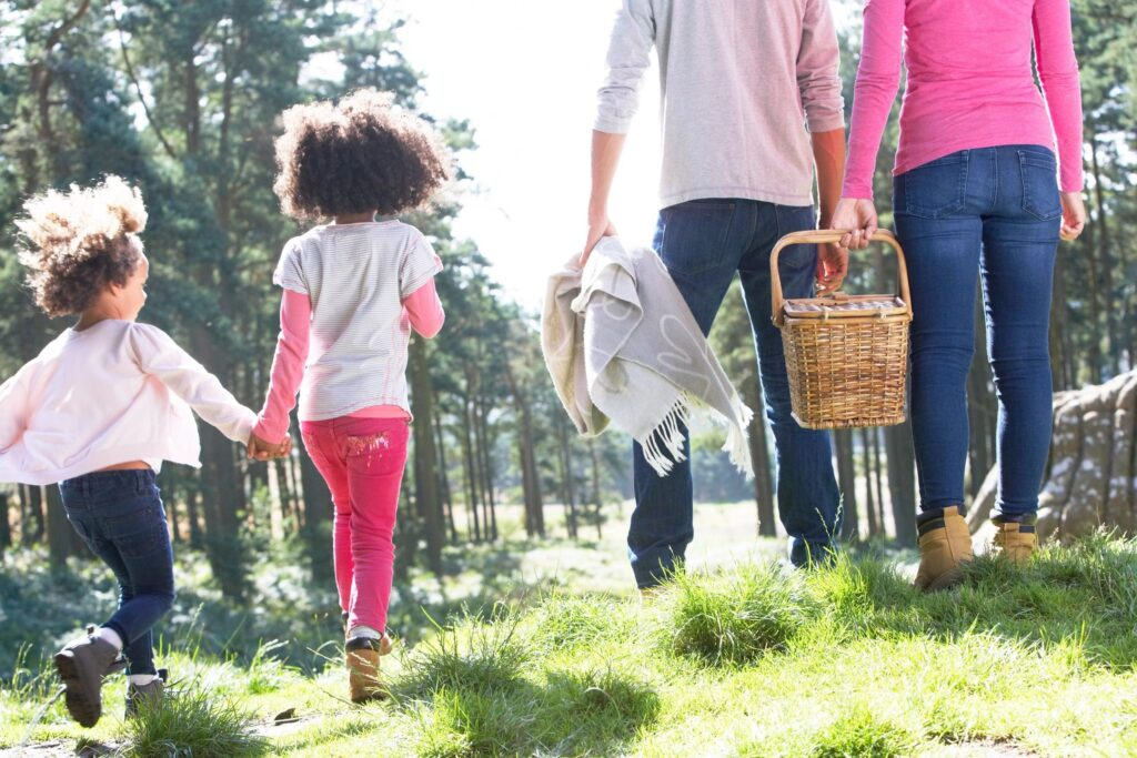 Couple walking with children to picnic.
