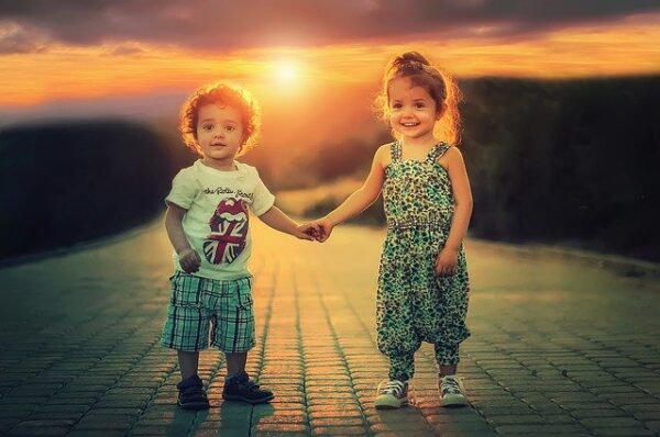 Two little kids holding hands.