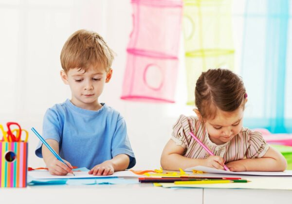 Boy and girl coloring with colored pencils.