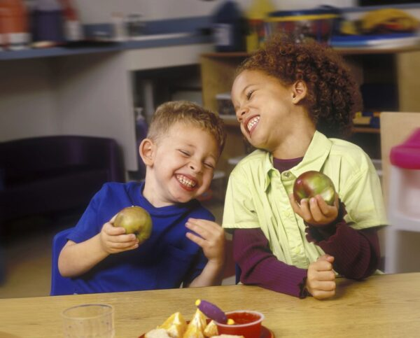 Boy and girl laughing and eating apples.