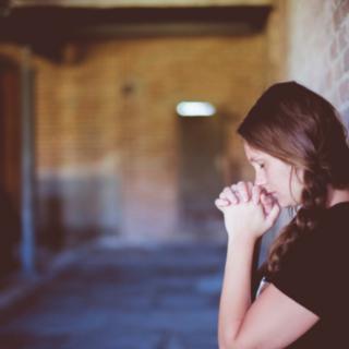 Woman praying in the church.