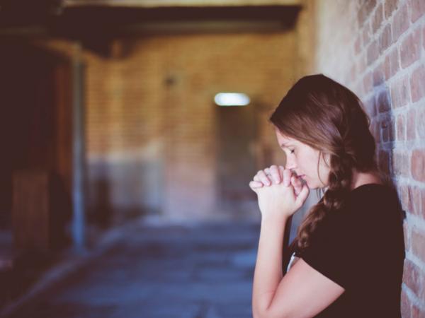 Woman standing in a church praying.