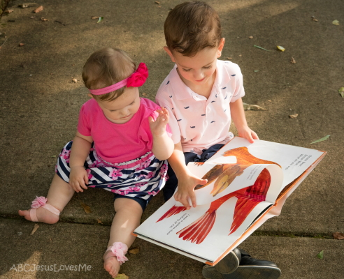 Young girl and boy look at a book.