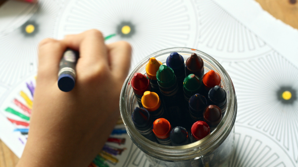 Child coloring with crayons.