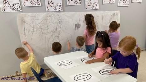 Preschool children coloring with a black crayon.