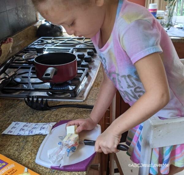 Preschooler cooking, cutting butter.