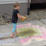 Child playing with water and sidewalk chalk.