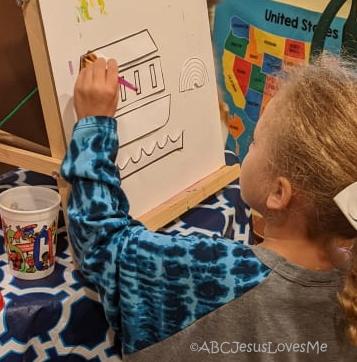 Preschool girl painting Noah's Ark craft.