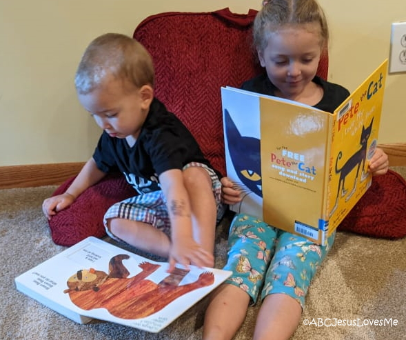 Preschool brother and sister reading books.