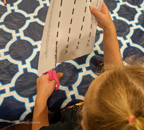 Preschool girl cutting with scissors.